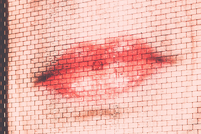 Photo of face and lips projected onto a brick wall. By Arun Kuchibhotla, from Unsplash