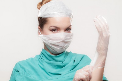 Cosmetic surgeon putting on surgical gloves